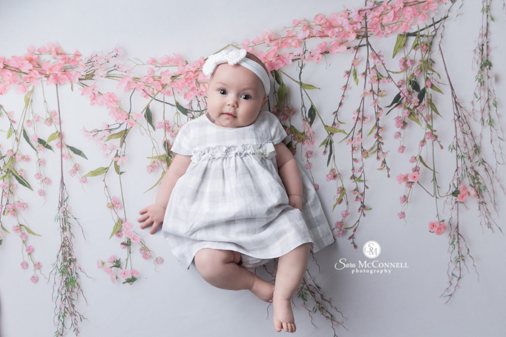four month old baby in a white dress in front of flowers
