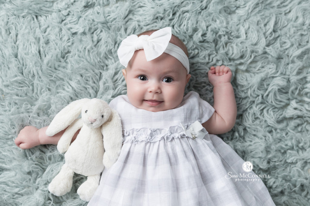 four month old baby in a white headband and dress with a bunny