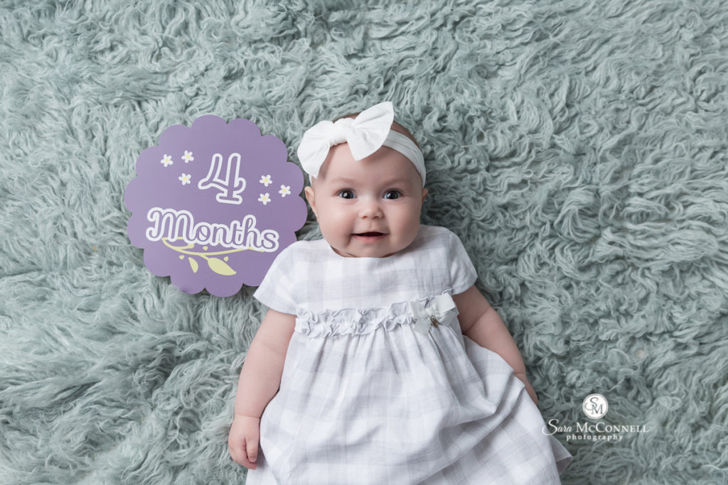 four month old baby with a sign that says 4 months
