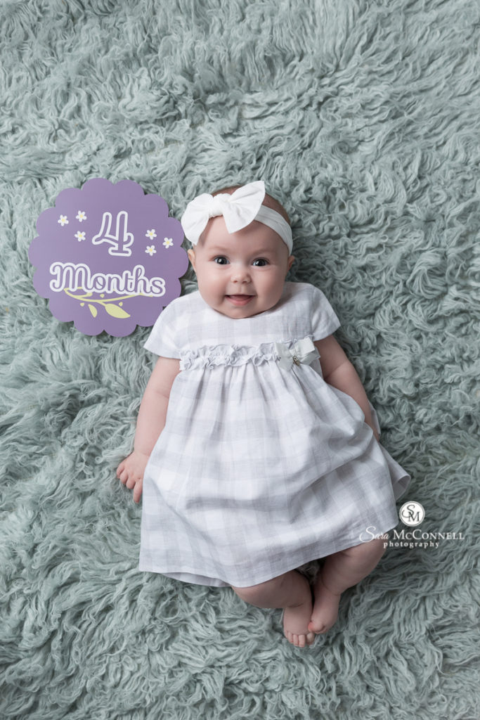 baby girl in front of a sign that says 4 months