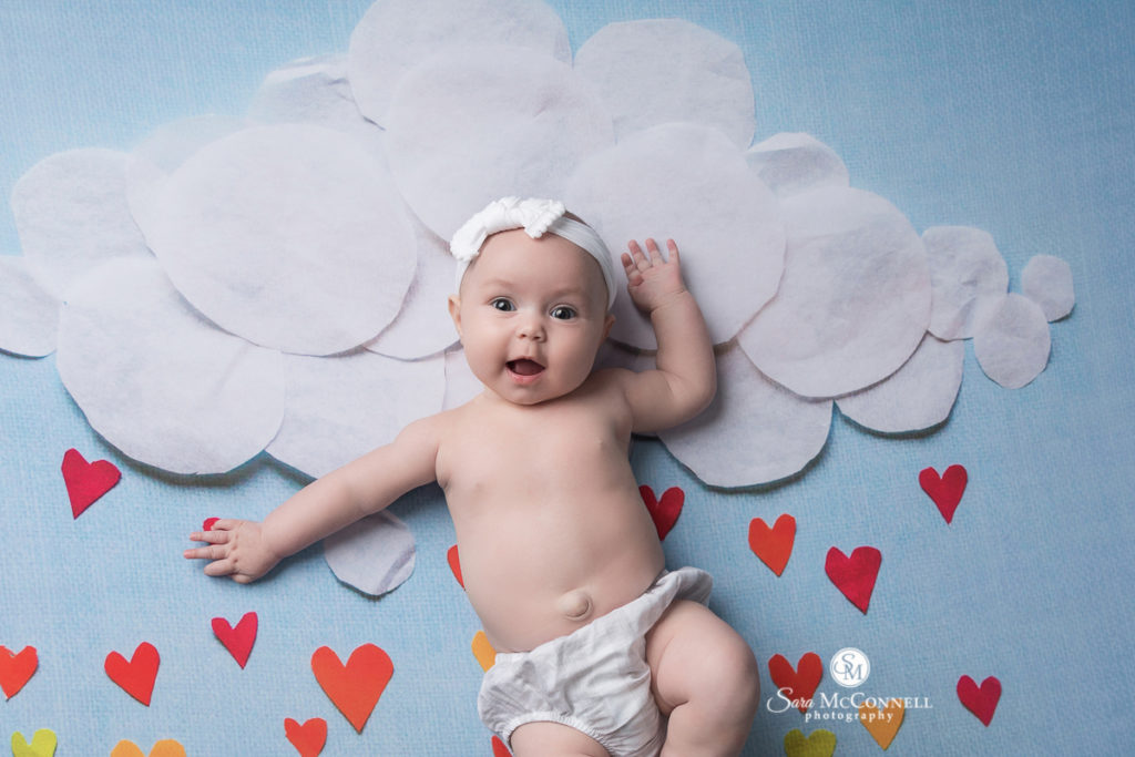 four month old in front of pretend clouds and rainbow showers