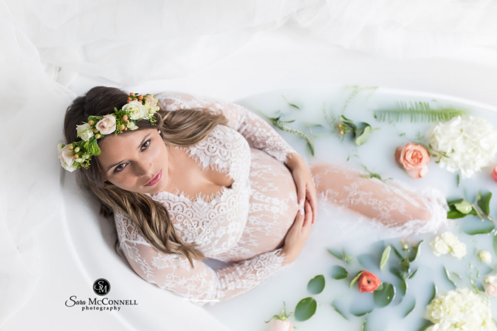 expectant mother in a milk bath surrounded by leaves and flowers
