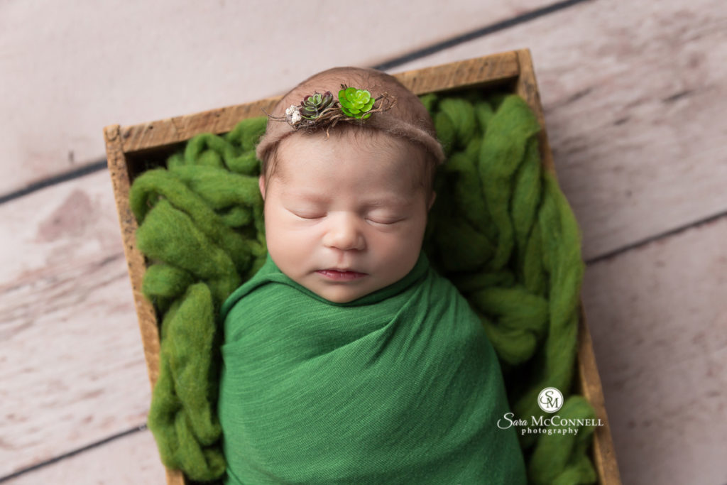 sleeping baby wrapped in green