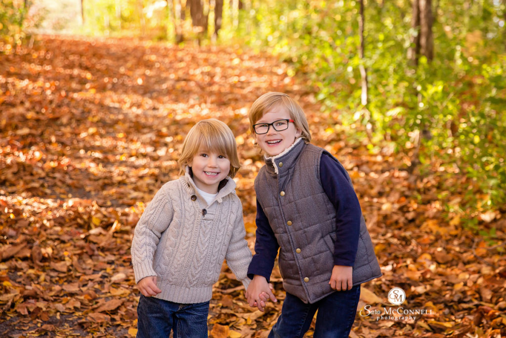 brothers holding hands on a path of leaves