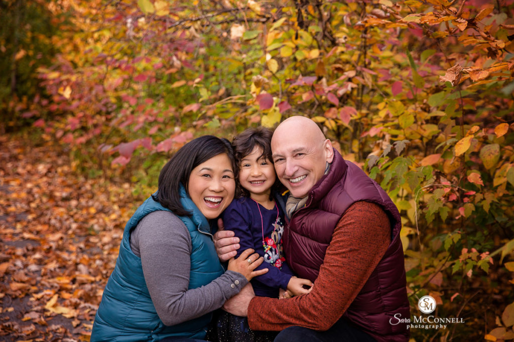 family snuggling outside in fall leaves
