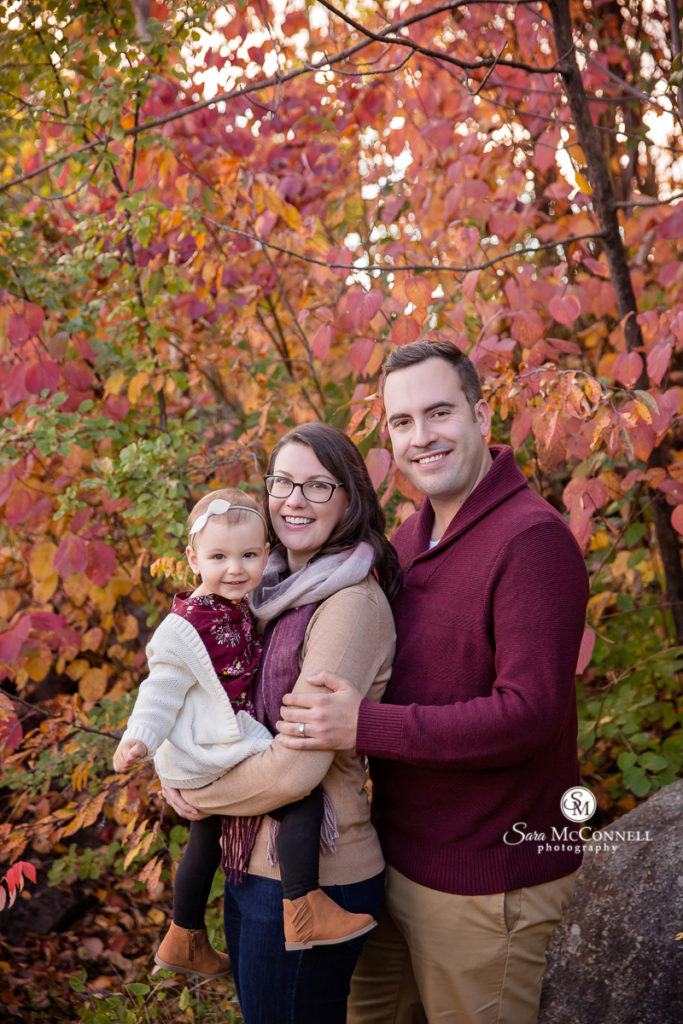 mom and dad holding toddler in front of red tree