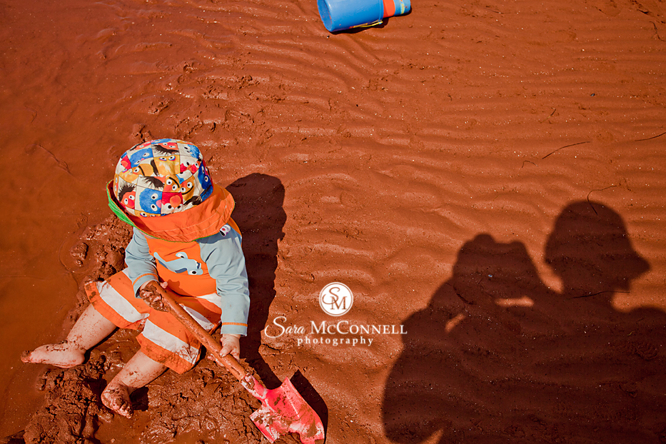 small boy playing in the red sand of pei