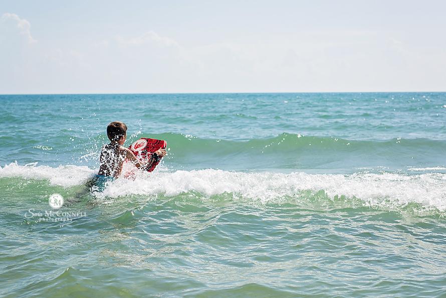 boy swimming in wavy water