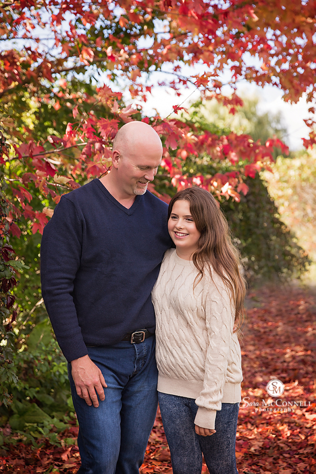 father and daughter in front of red tree