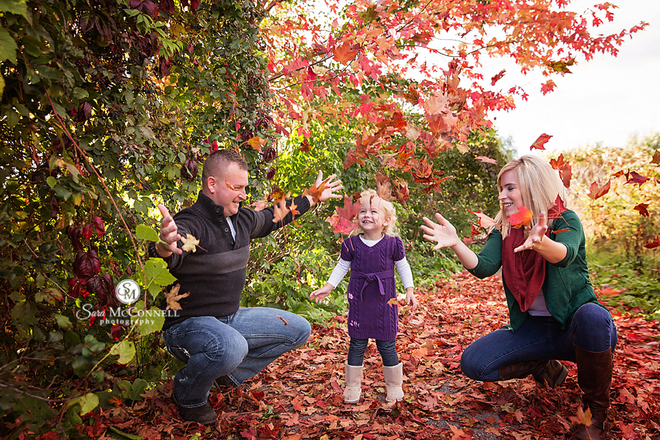 parents tossing leaves in the air in front of their child