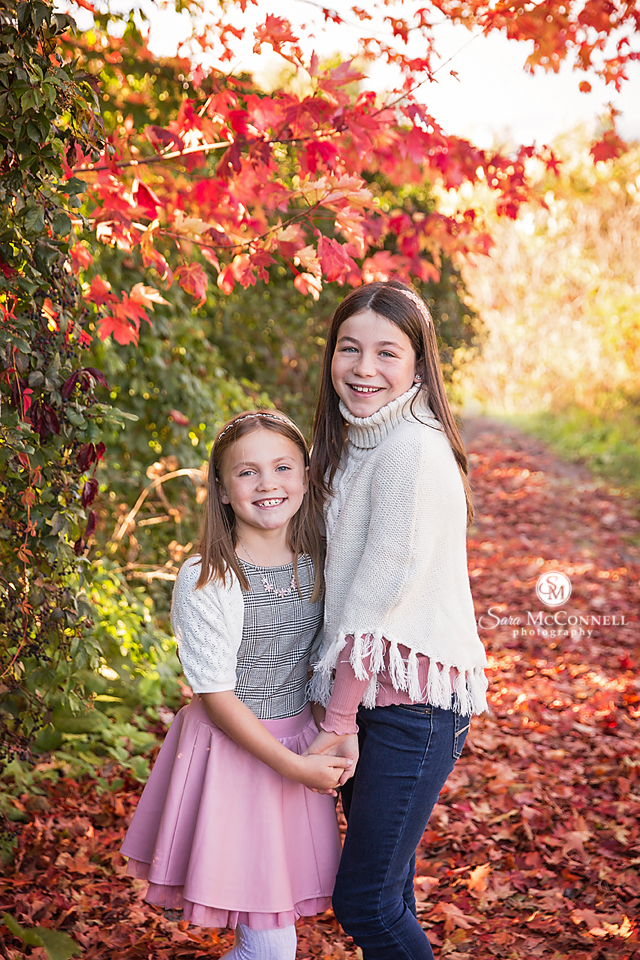 sisters holdings hands on a path with fall leaves