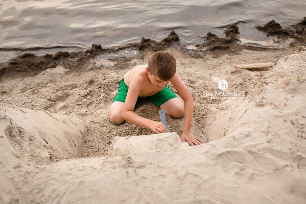 teenager digging in the sand