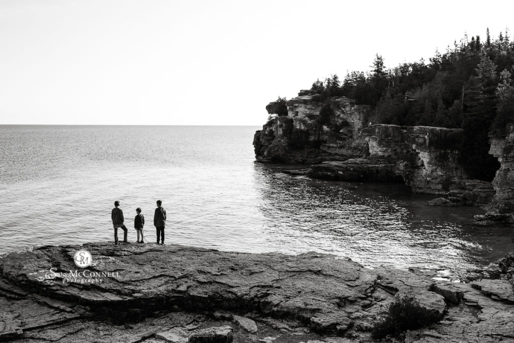 brothers standing on a rock looking at a lake