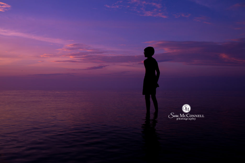 silhouette of a boy standing in water