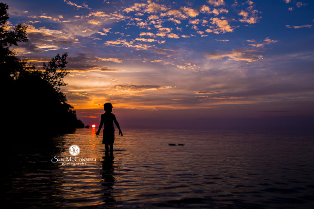silhouette of a young child standing in water at sunset