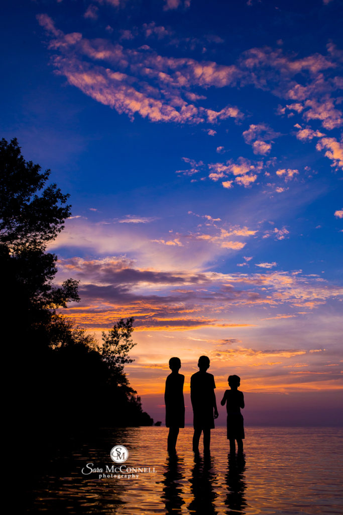 silhouette of three brothers standing in water at sunset