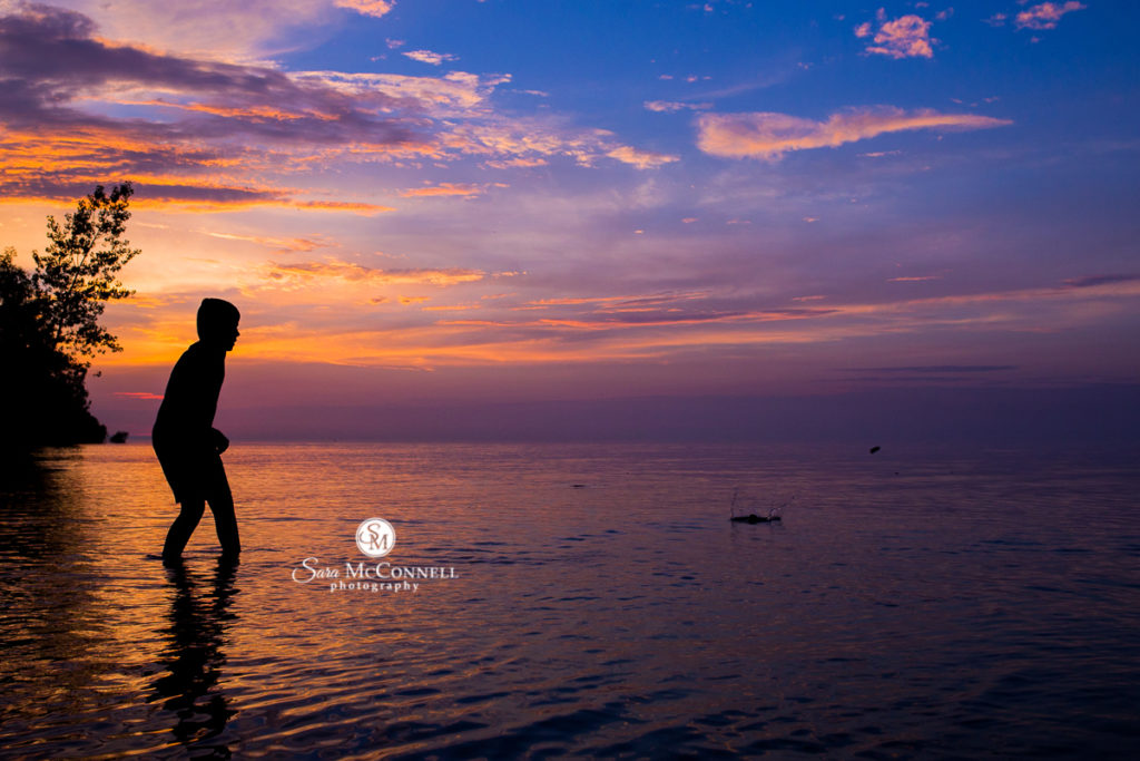 silhouette of a teen standing in water at sunset