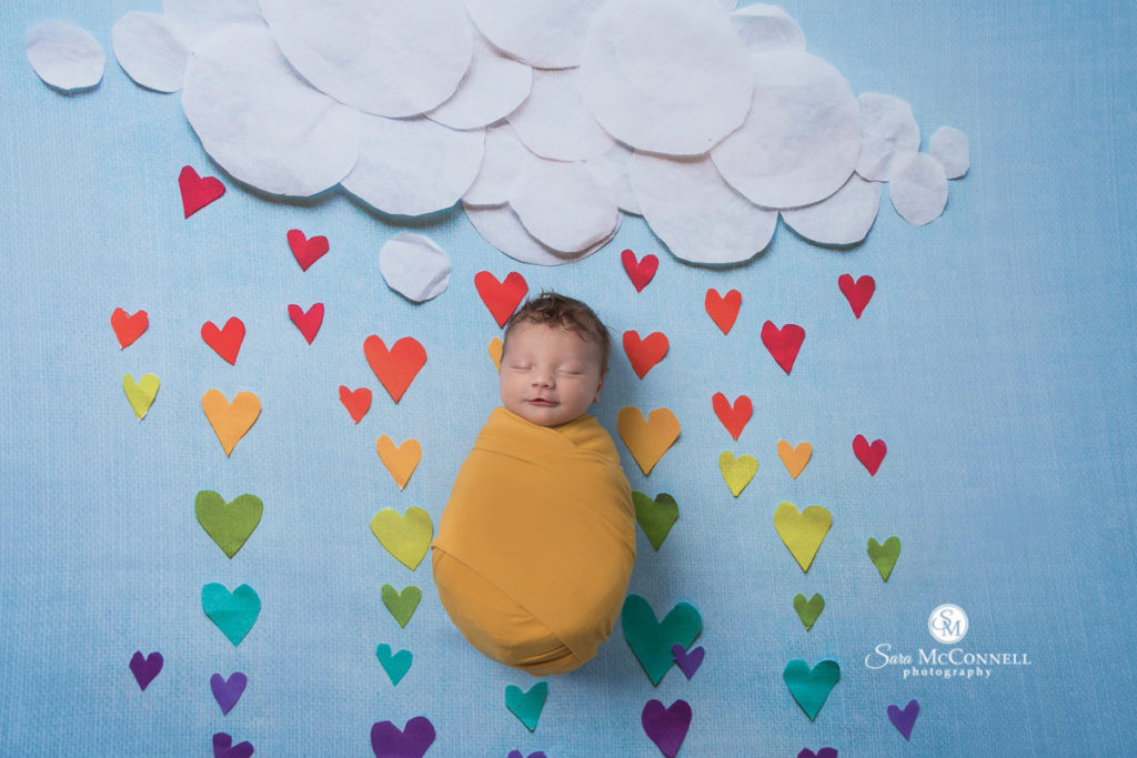 sleeping baby wrapped in orange with paper clouds and coloured rain