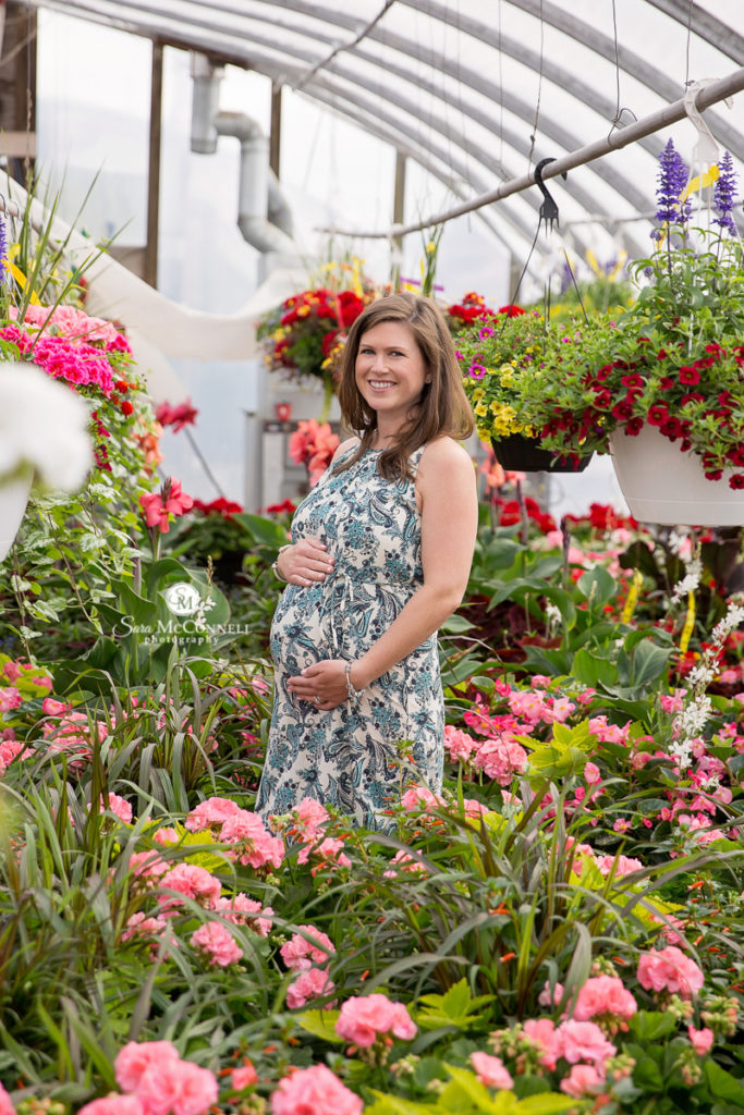 pregnant woman cupping her belly in a greenhouse
