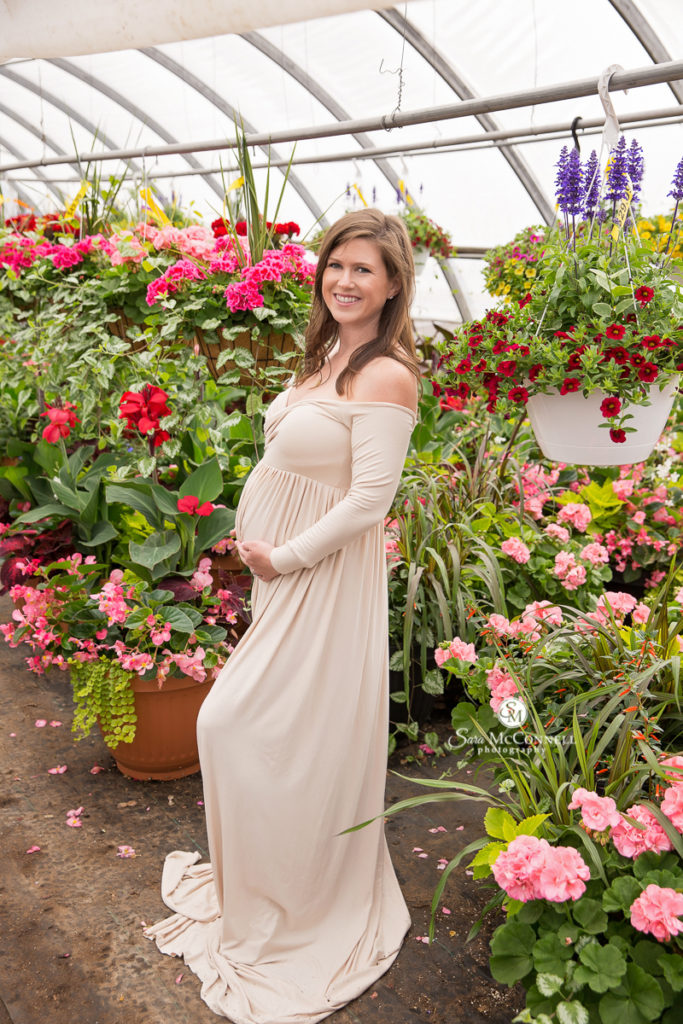 pregnant woman wearing a beige dress in a greenhouse