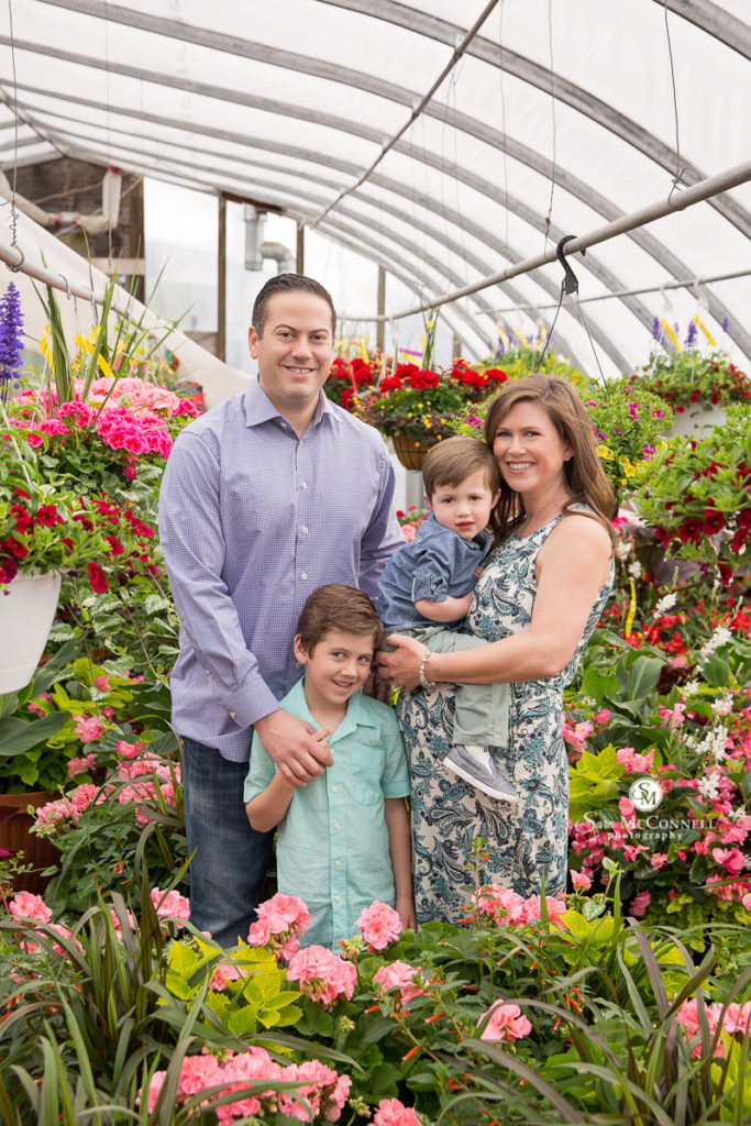 parents with two sons in a greenhouse