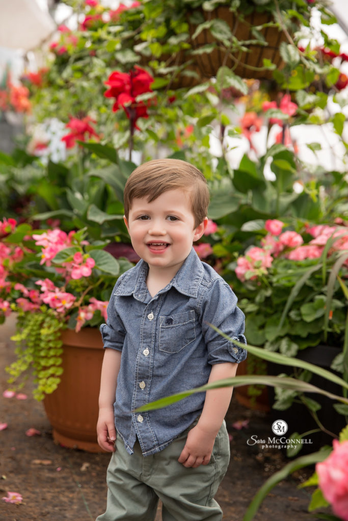 young boy in a chambray shirt in front of flowers