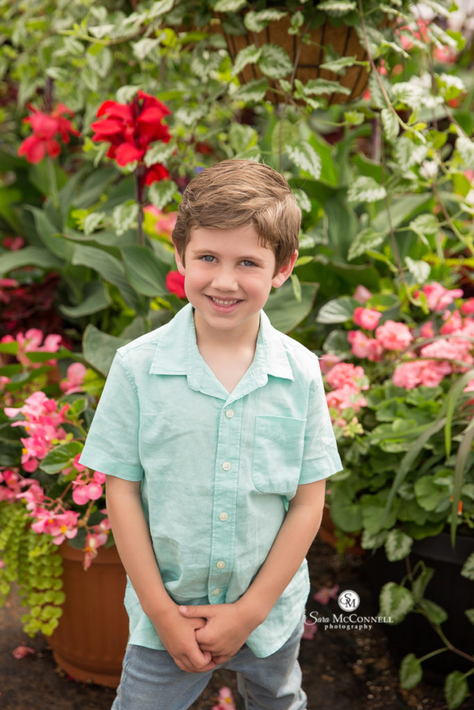 boy in a button up t-shirt in front of flowers