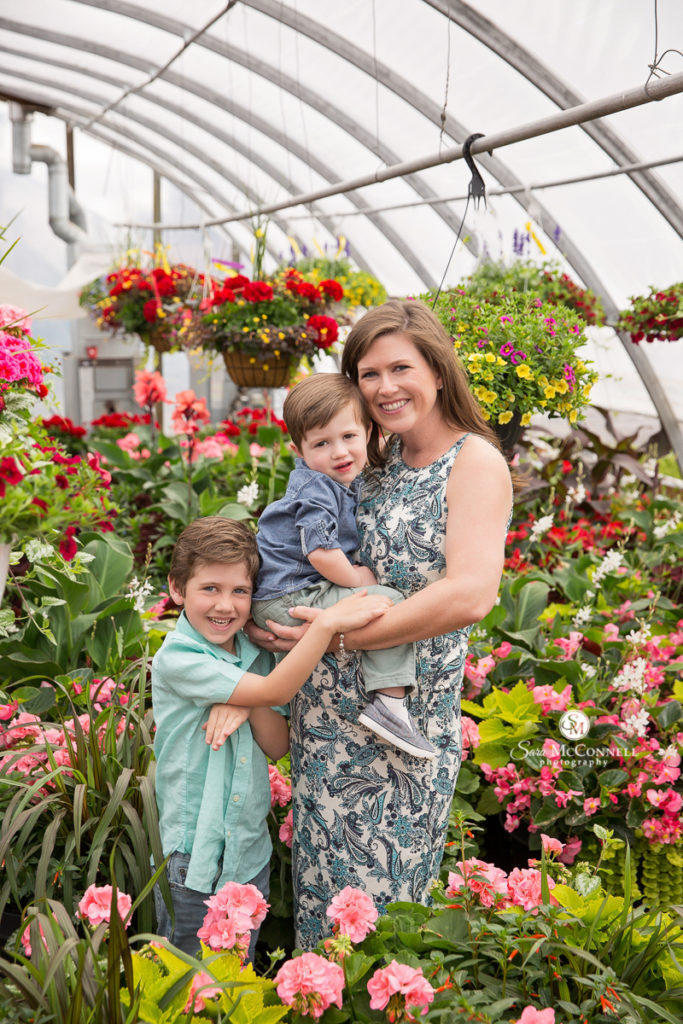 pregnant mother with two sons in a greenhouse