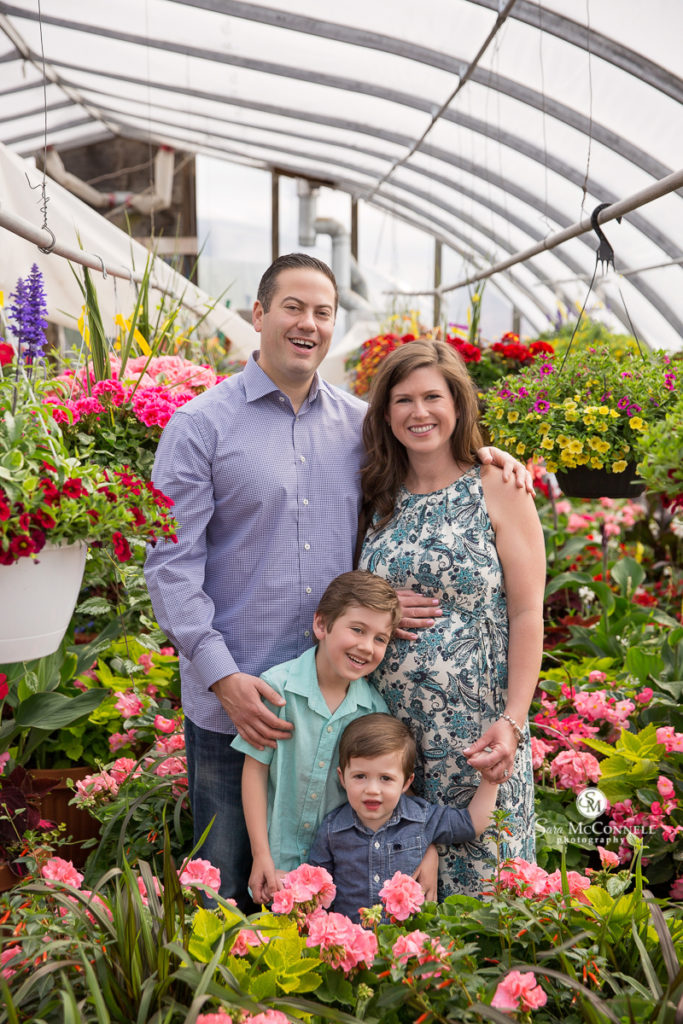 family of four in a greenhouse
