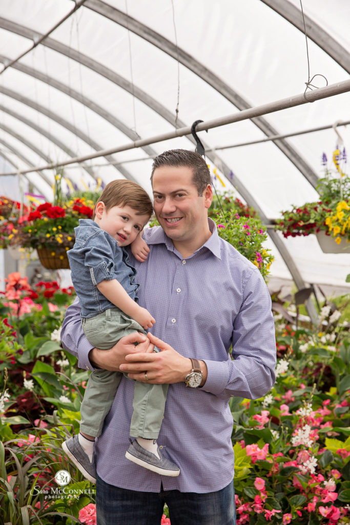 dad holding son in a green house