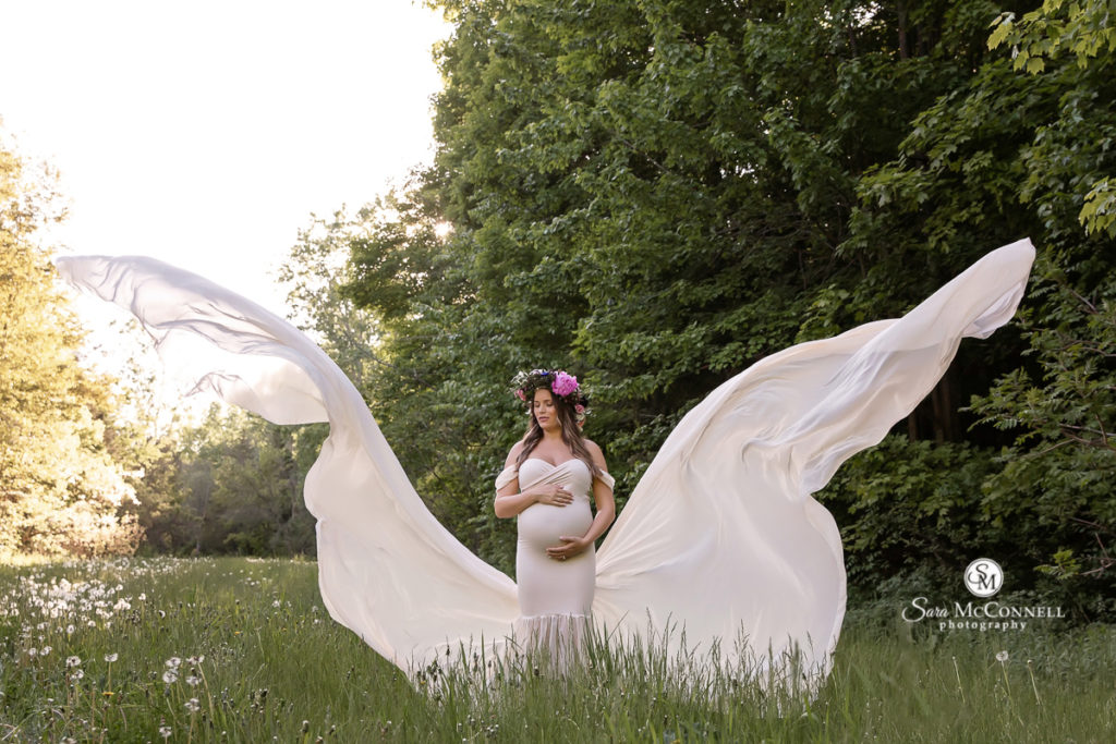 pregnant woman outside in a flowing white gown