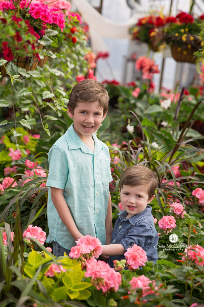 two brothers in a greenhouse smiling for a photo