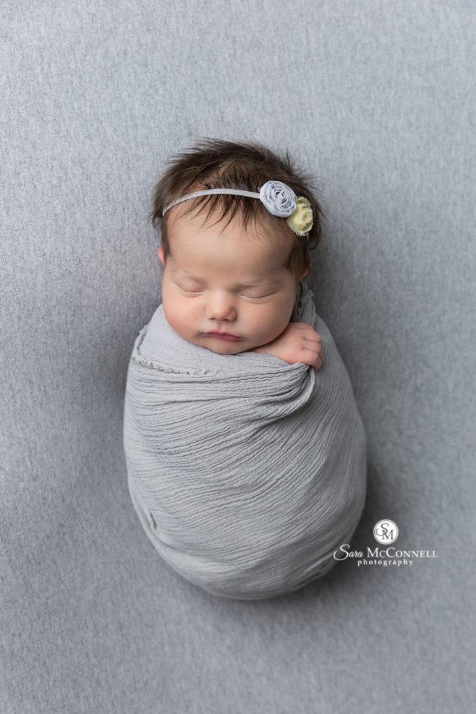 sleep newborn baby wrapped in a grey blanket