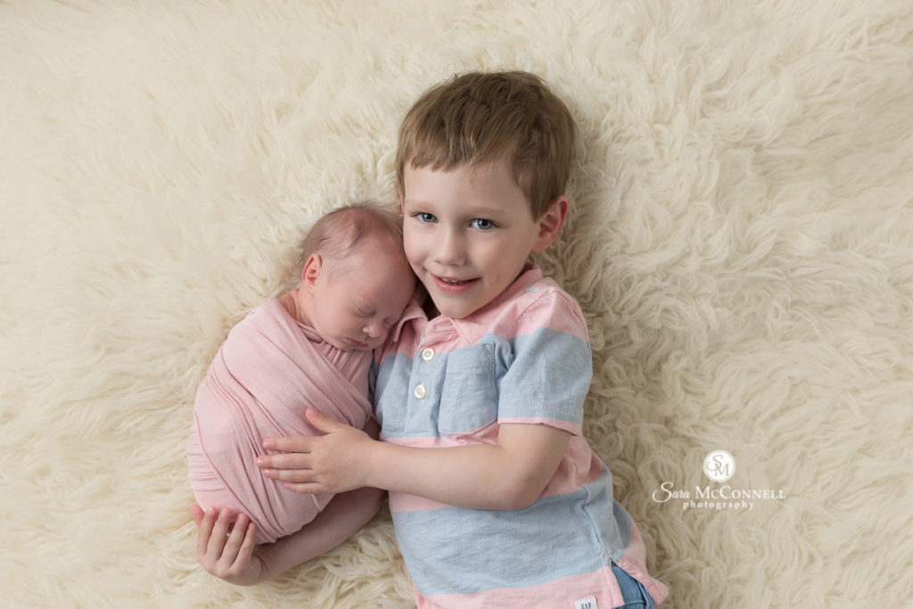 brother snuggling with baby sister