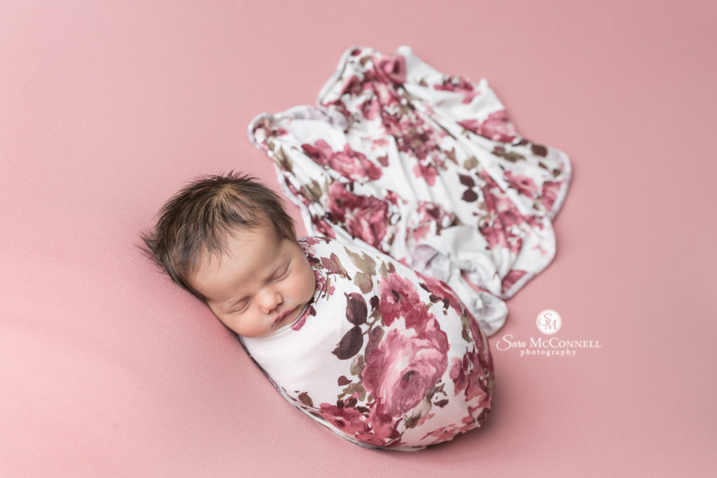 sleeping baby wrapped in floral cloth