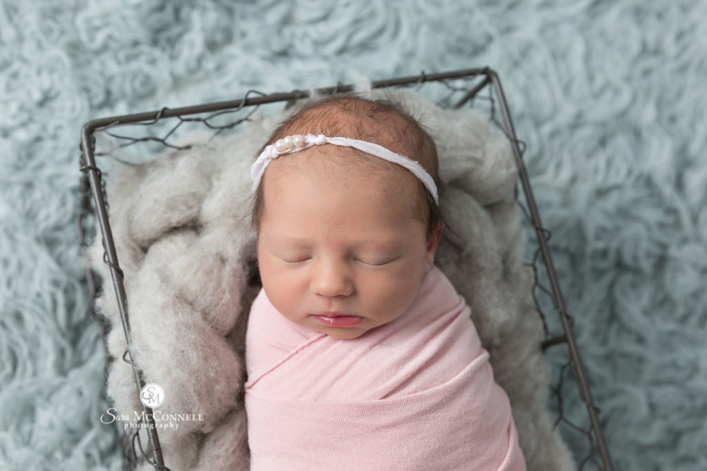 newborn baby girl wrapped in pink