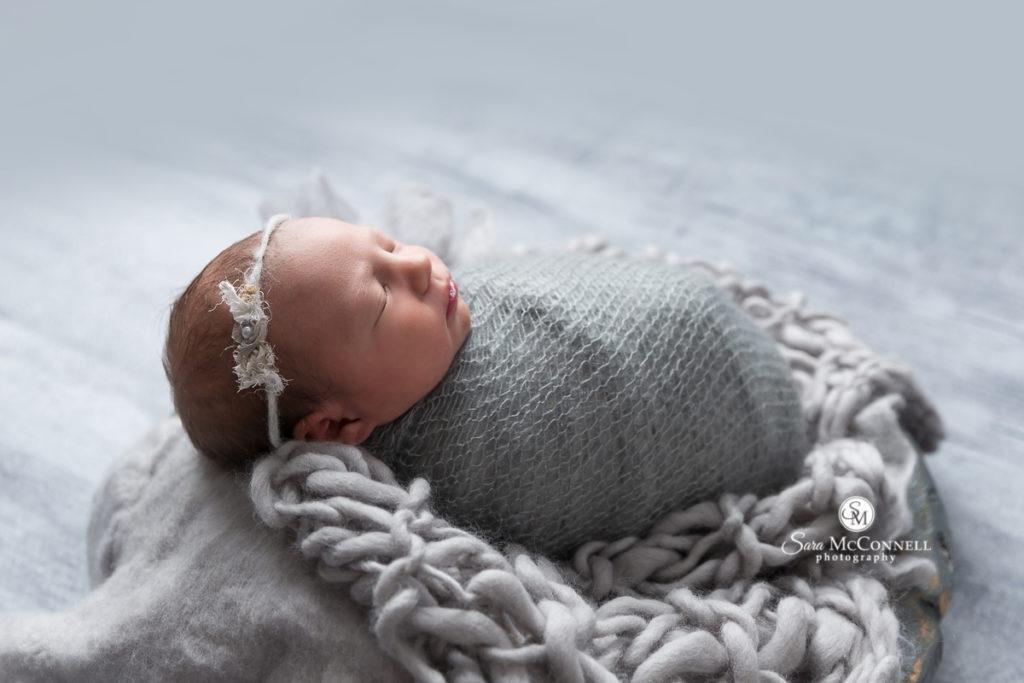 newborn wrapped in grey