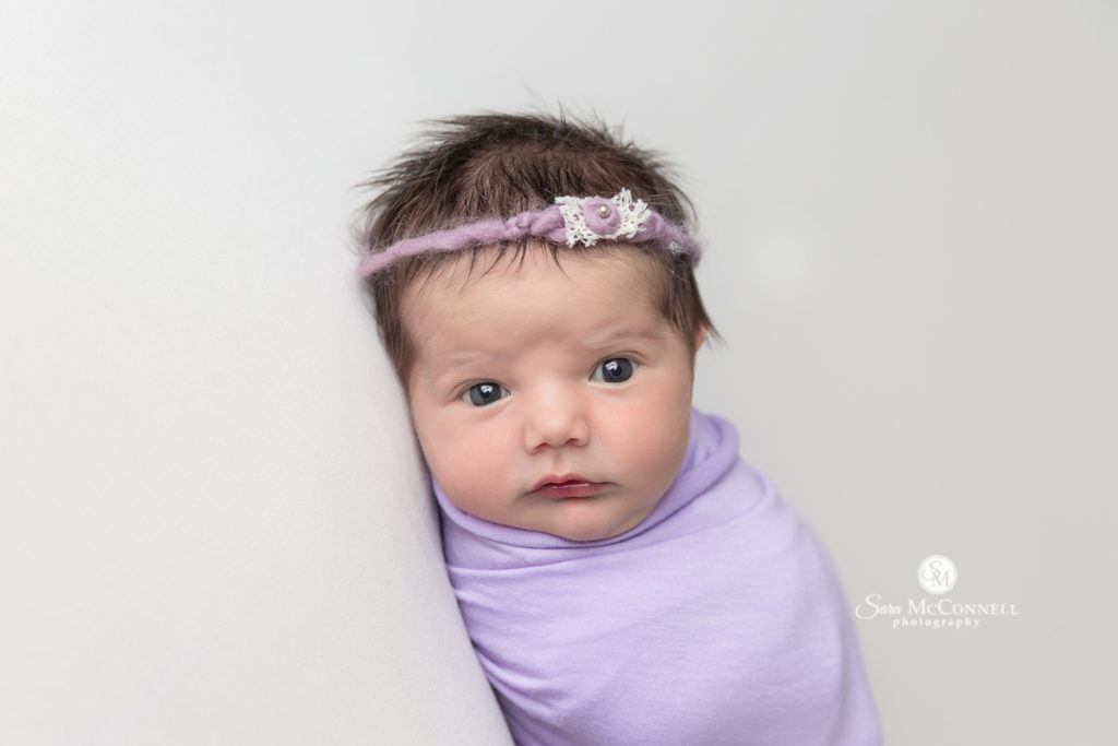 baby with eyes open wearing a headband and wrapped in purple
