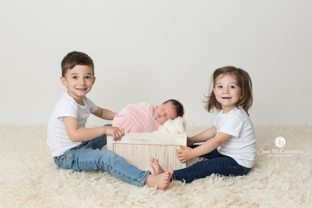 brother and sister with newborn baby sister