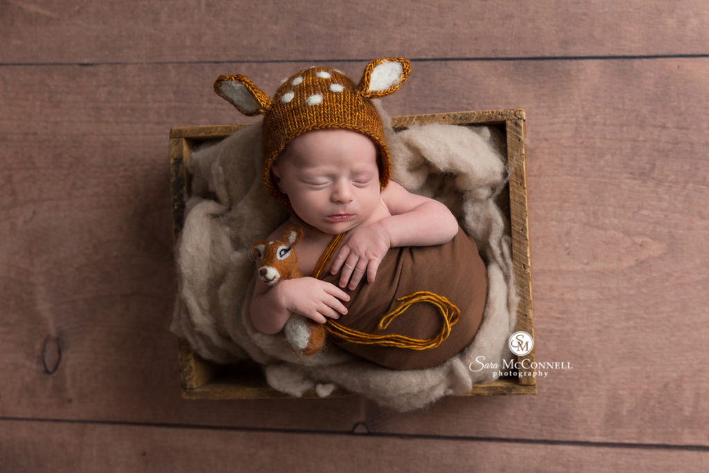 sleeping newborn baby wearing a knitted deer hat