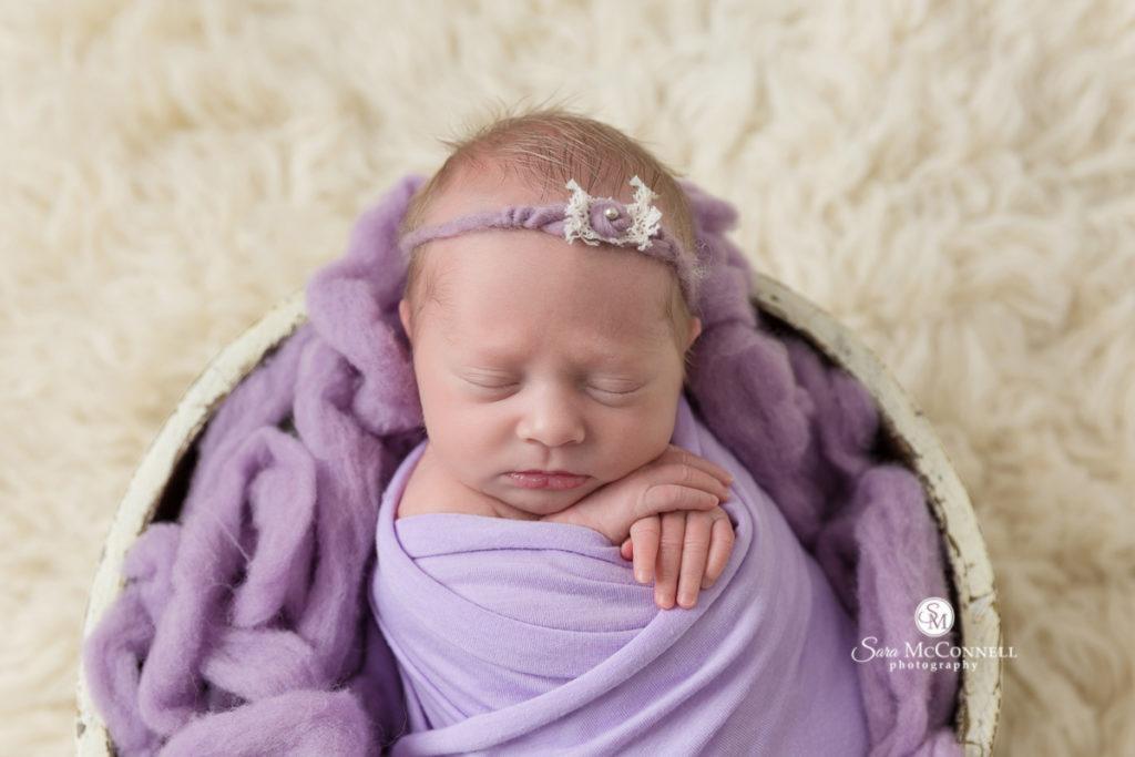 newborn baby girl wrapped in purple