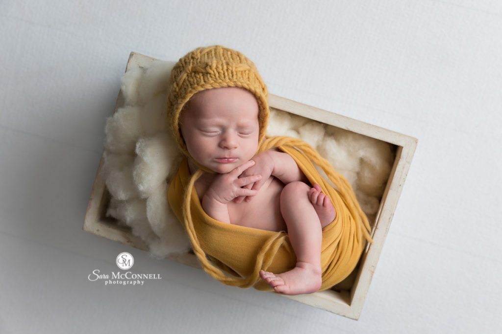 newborn baby sleeping while wearing a knitted yellow hat