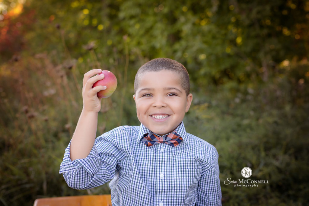 boy holding an apple for outdoor back to school photos in ottawa