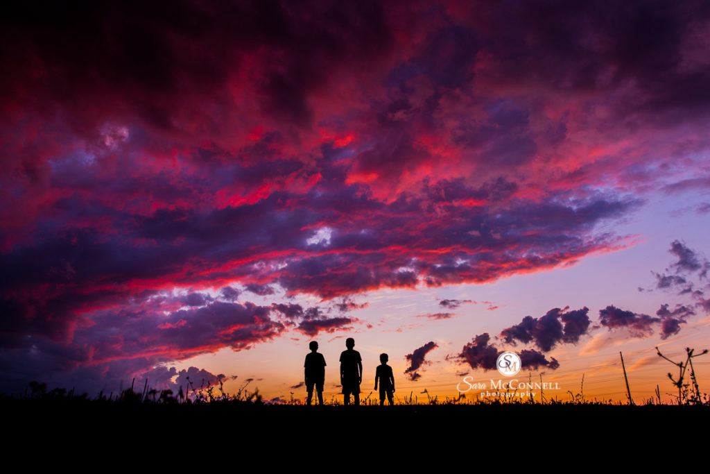 three boys in silhouette at sunset
