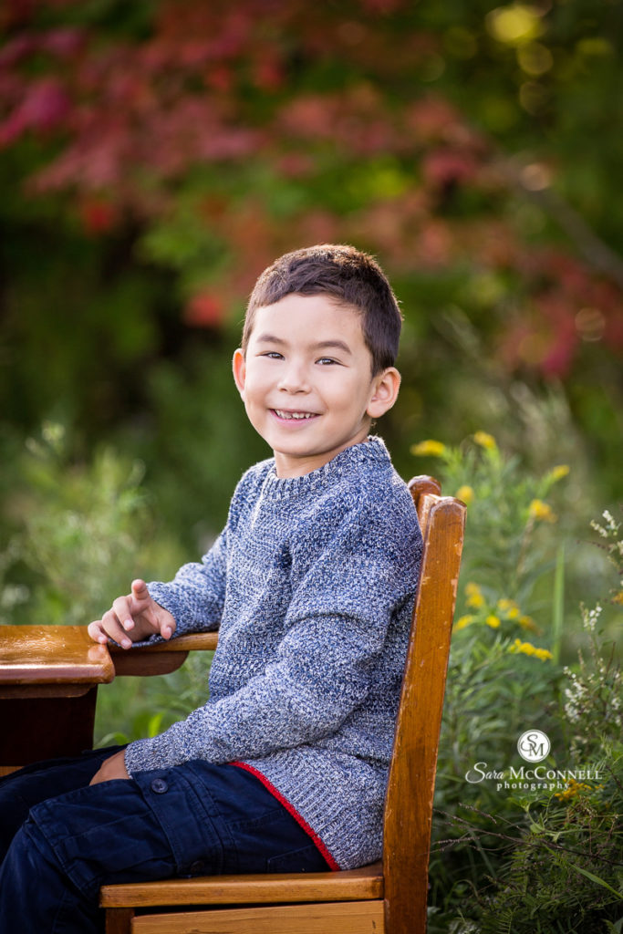 boy sitting on wooden desk outside for back to school photos