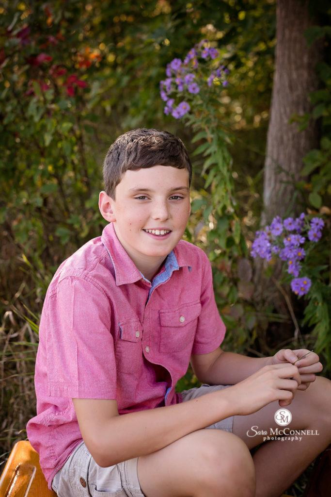 boy sitting outside smiling