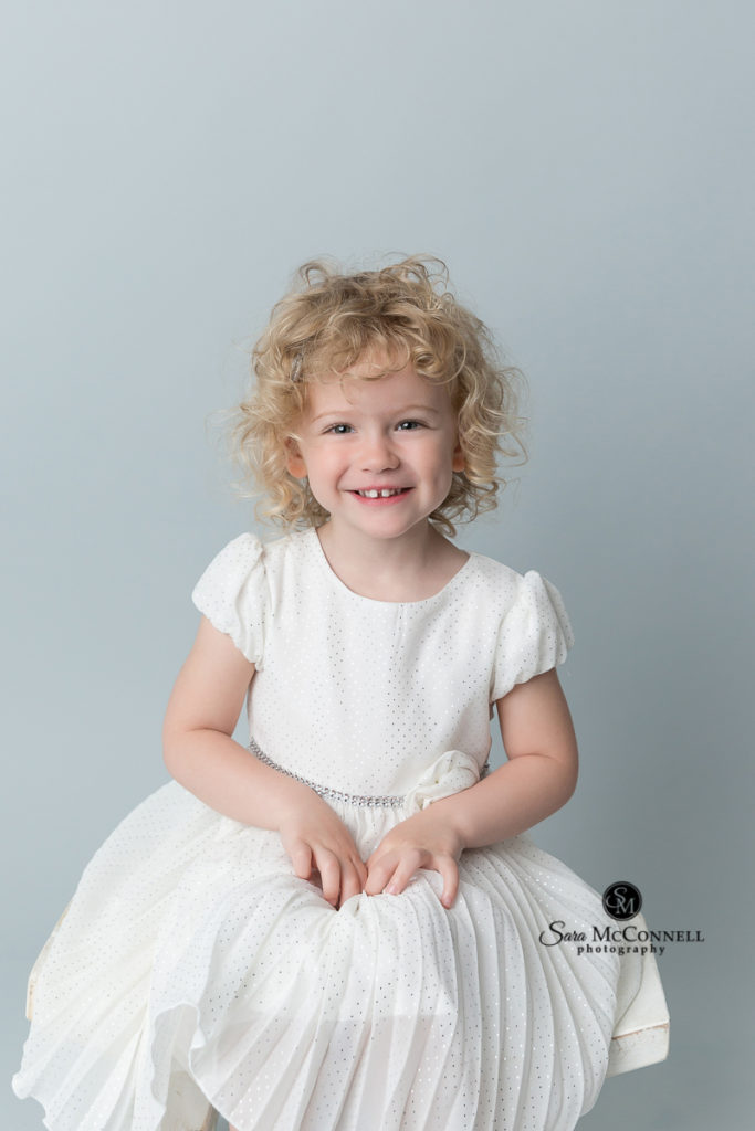 three year old wearing a white dress