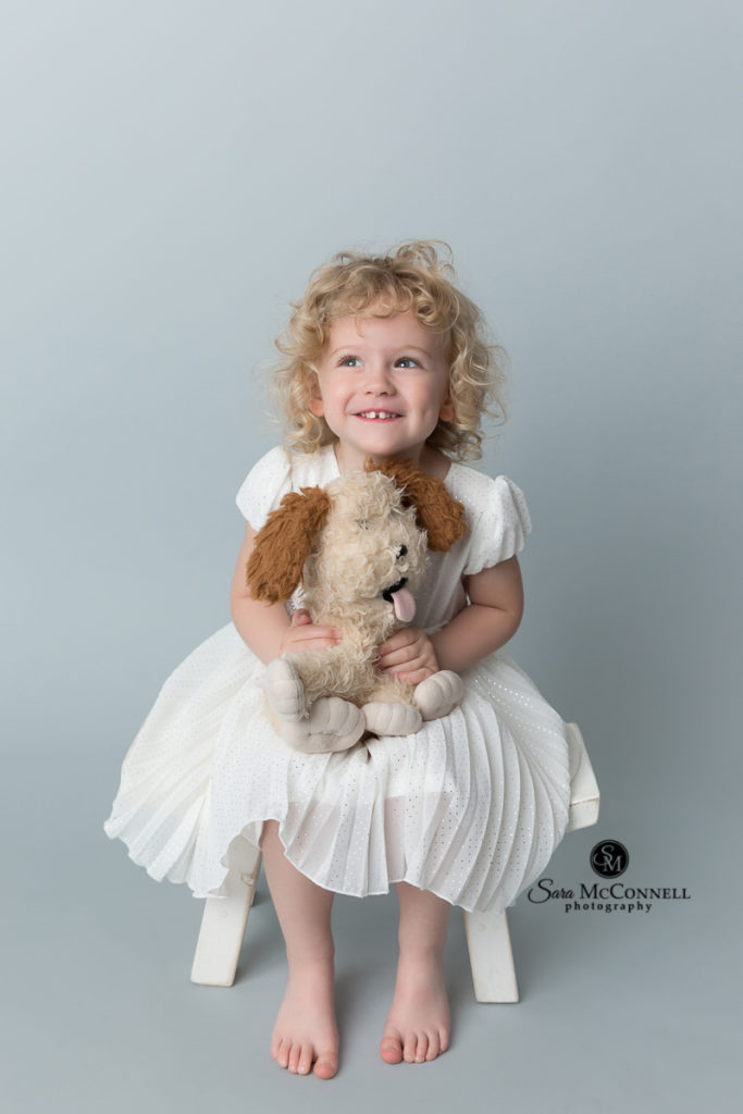3 year old wearing a white dress holding a stuffed puppy