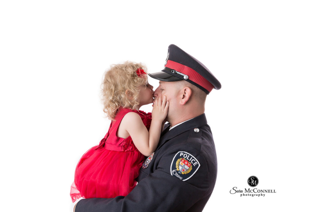 father in a police uniform holding his three year old daughter in a red dress