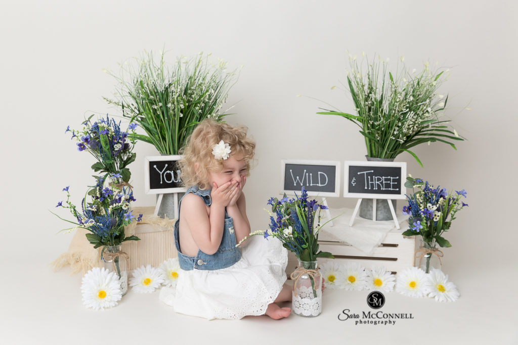 three year old in front of signs that say young wild and three